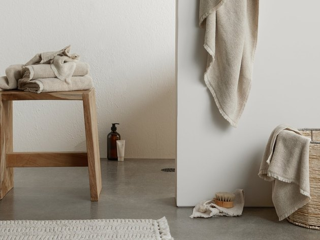 bathroom space with stool and basket and neutral towels