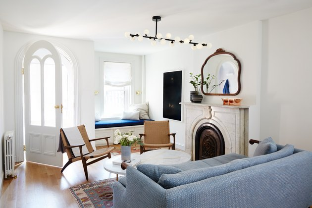 townhouse living room with modern pendant light and traditional fireplace