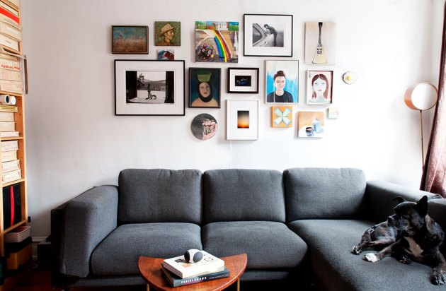couch with picture frame collage wall above