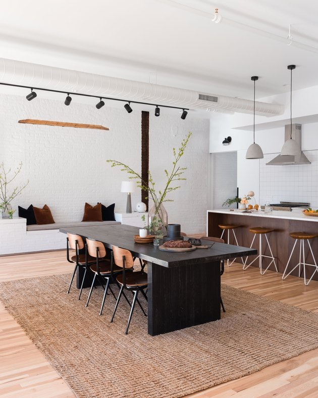 kitchen dining combination with modern track lighting and jute rug