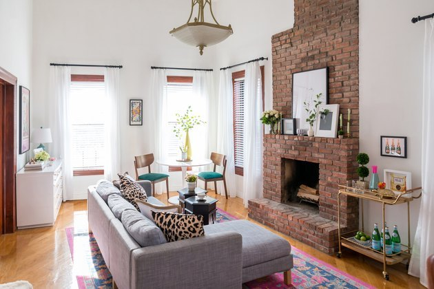 living room with brick fireplace and bar cart
