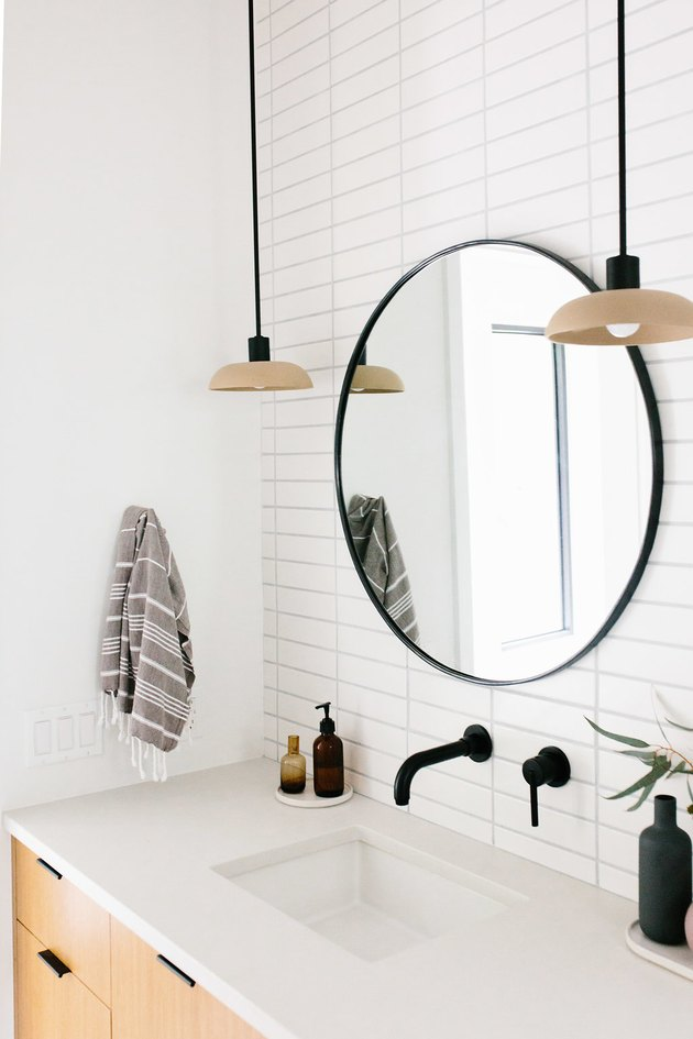 bathroom mirror idea with circle mirror with black frame and white metro tiles in bathroom