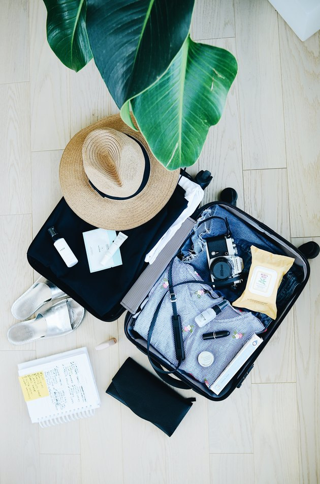 black luggage with clothes and camera
