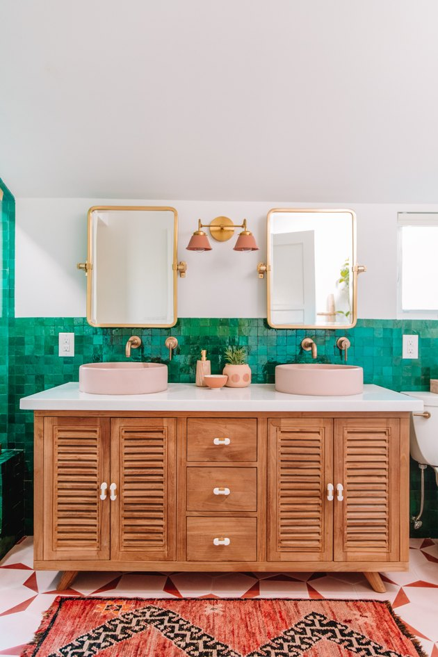 bathroom mirror idea with bright bathroom with wooden vanity, pink sinks, green tiles and gold mirrors