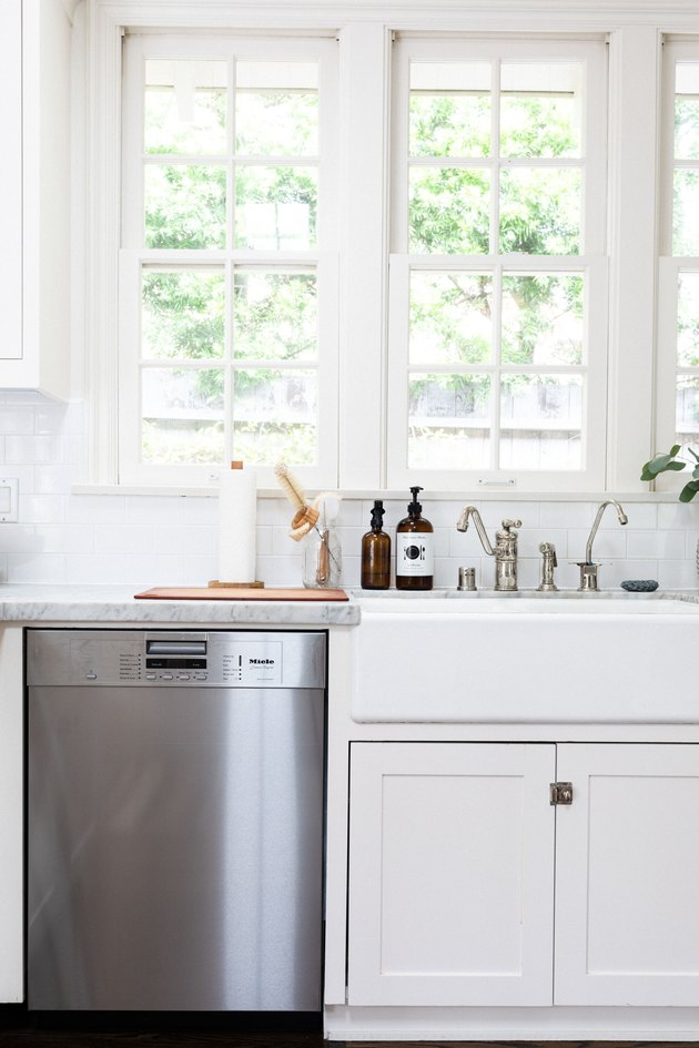 chrome dishwasher next to a farmhouse sink