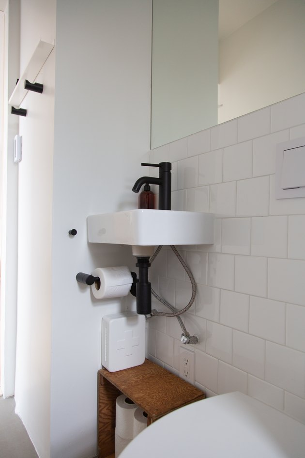 A recessed mirror and concrete floors in the bathroom.