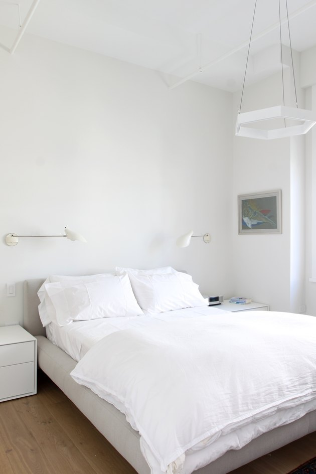 minimal bedroom with sconces and pendant light