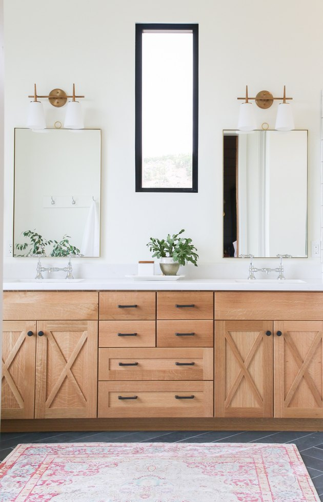 bathroom mirror idea with wooden vanity with thin brass framed mirrors and vintage light fittings