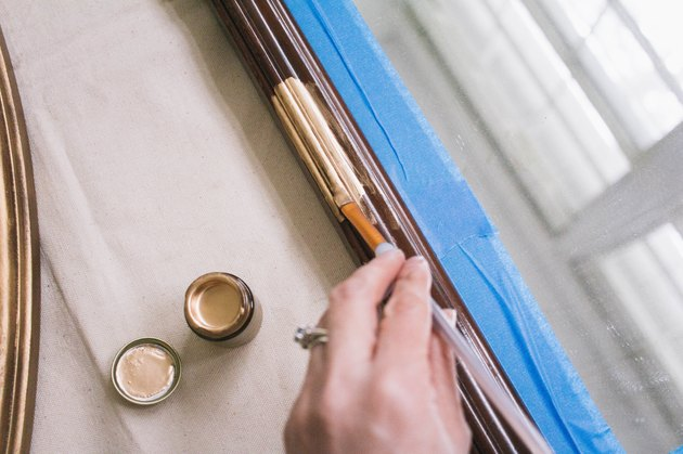 Painting gilding paint onto wooden mirror frame with small paintbrush