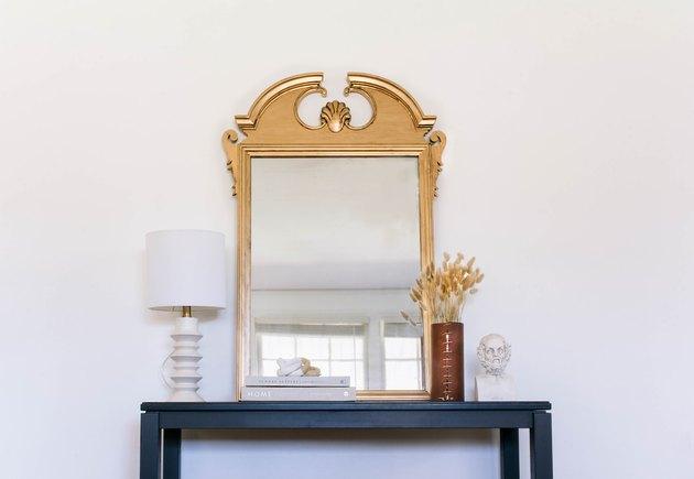 Miroir doré antique bricolage accroché au mur au-dessus d'une table noire avec lampe, livres et vases