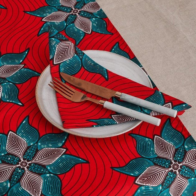 red patterned napkins with one dish, fork, and knife