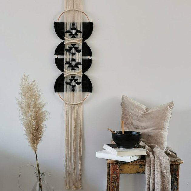 wall hanging near stool with blanket and books