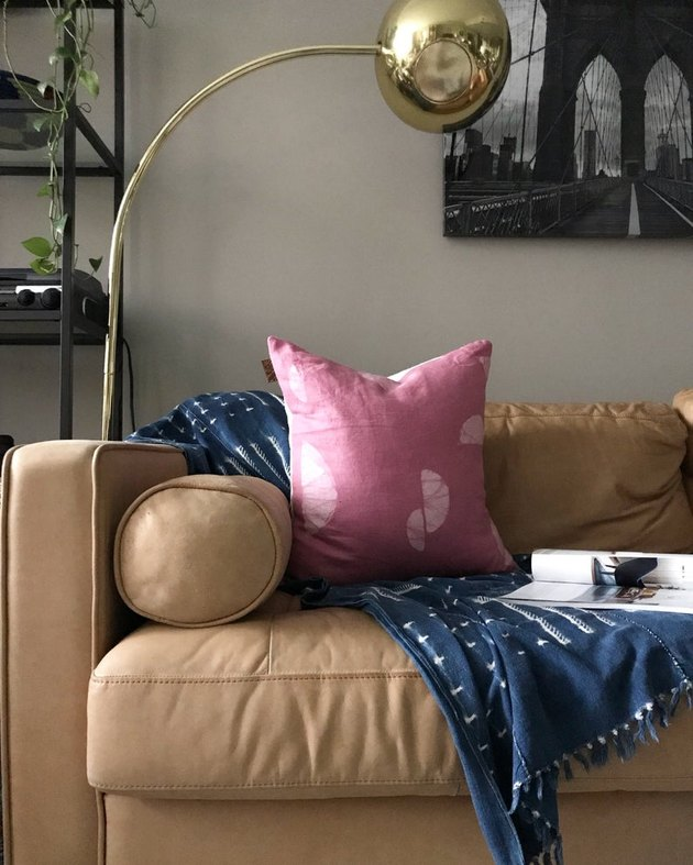 beige couch with gold floor lamp, pink pillow, and blue blanket