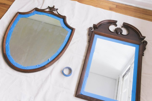 Two wooden thrift store mirrors with painter's tape around edges of frame