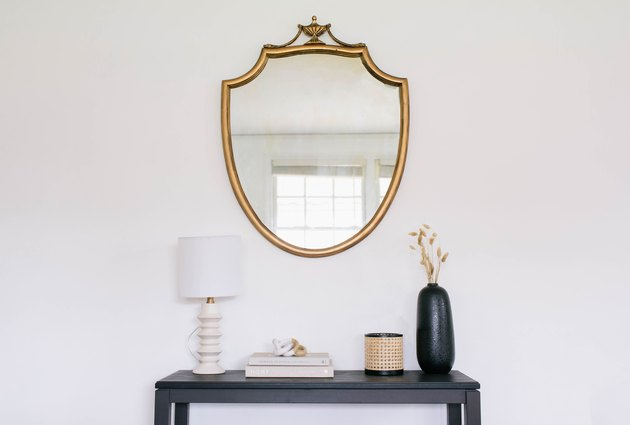 DIY gilded mirror hanging on wall above black table with lamp, books, and vases