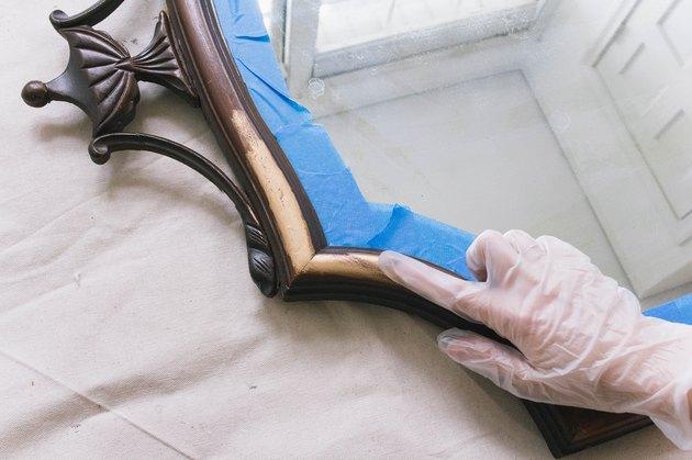 Frotter la cire de dorure sur un cadre de miroir en bois avec un gant en latex