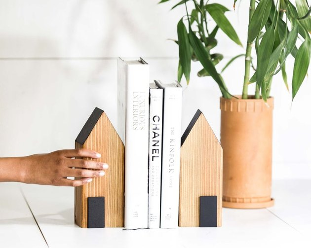 person placing bookend in shape of a house near books and other matching bookend