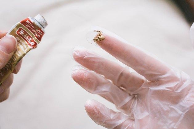 Quantité de cire de dorure de la taille d'un pois pressée sur le bout des doigts ganté