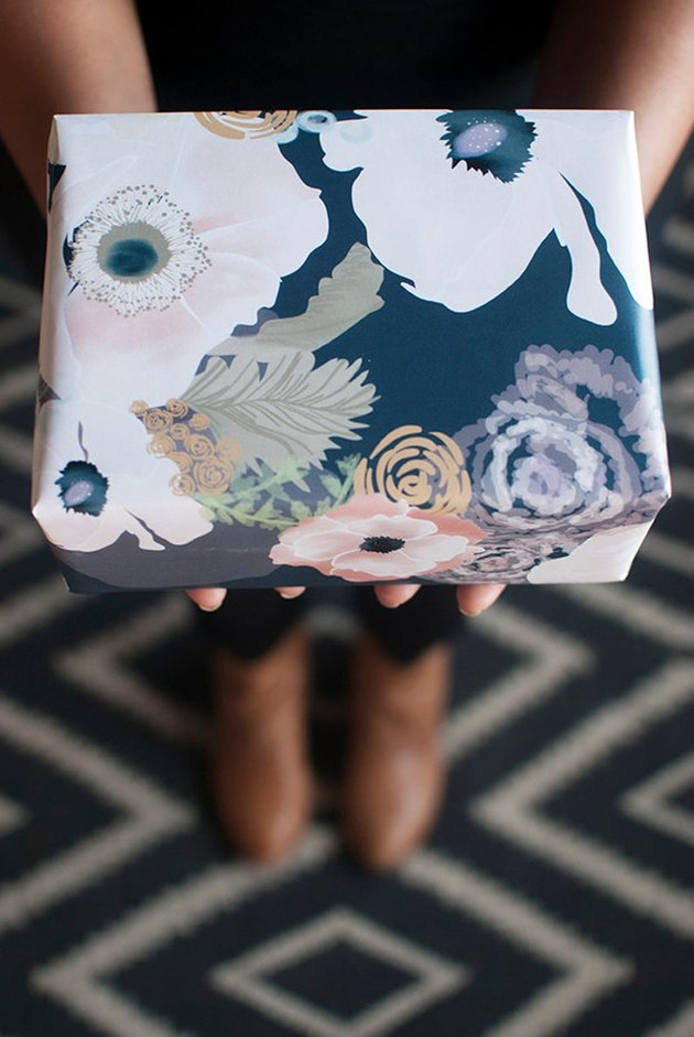 person holding a gift wrapped in floral gift wrap