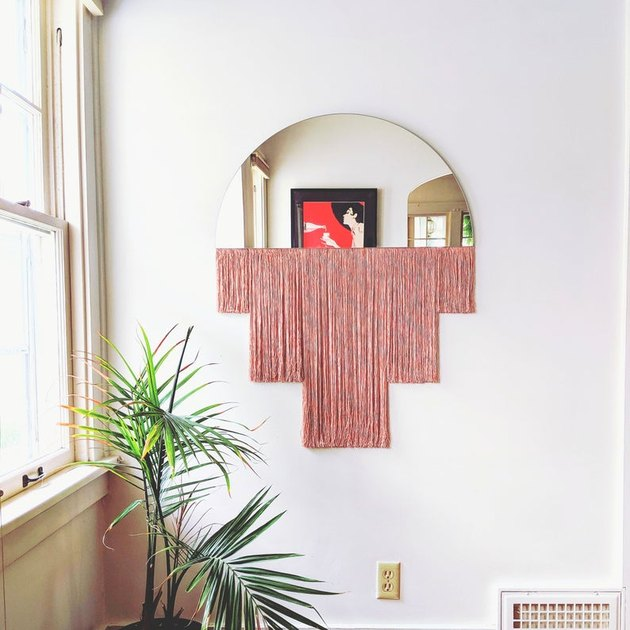 mirror with pink fringe with plants nearby