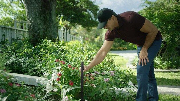 man putting wireless post into garden