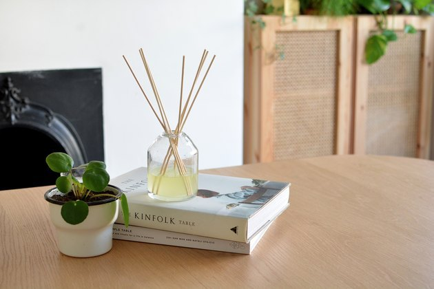 Reed diffuser on table with stack of books