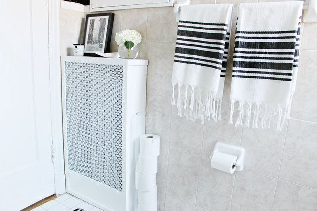 White radiator cover in bathroom with black and white towels