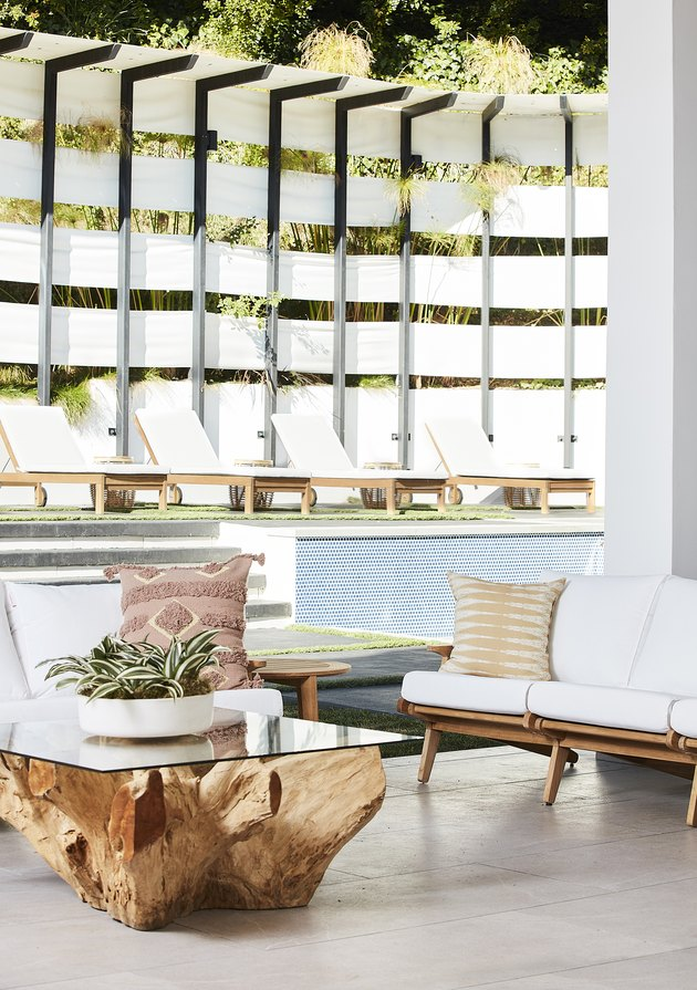 bright outdoor space with white furniture by pool