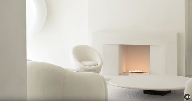 living space with all white walls and white furniture, with fireplace