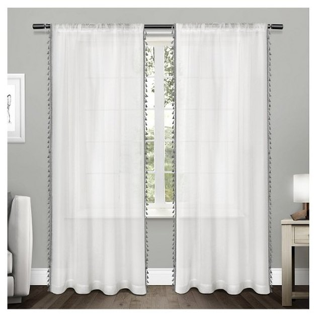 Sheer white curtain panels with small black tassels lining the outer border
