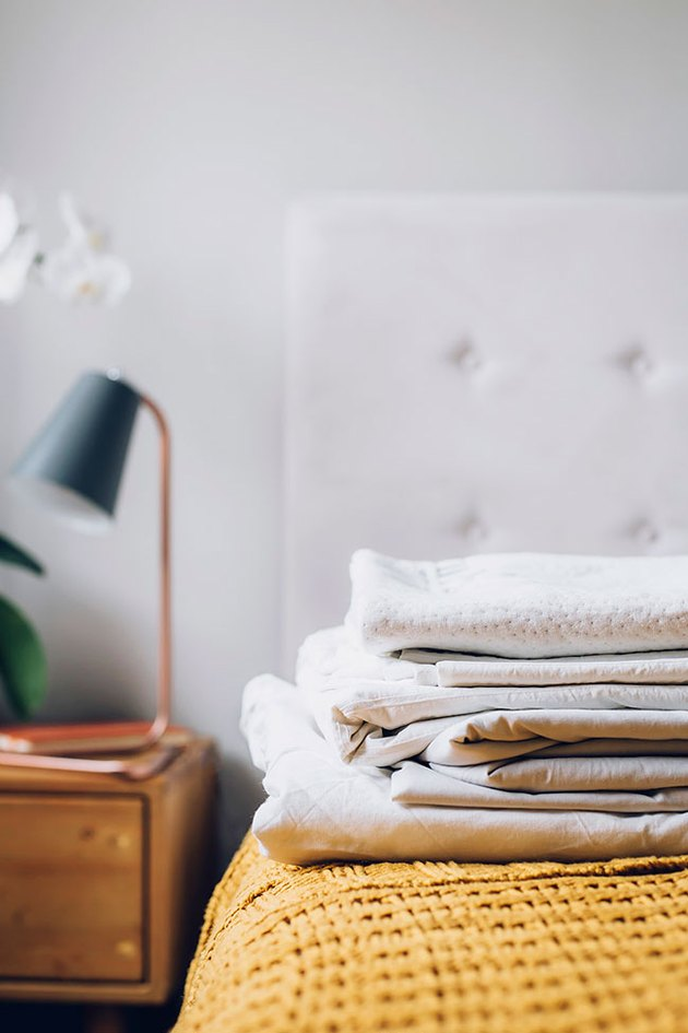 Stack of folded bed sheets on a bed