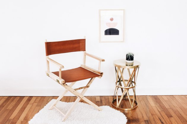 Leather director's chair next to brass side table on white rug