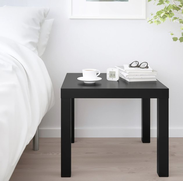 IKEA's LACK side table in black next to a bed with white bedding