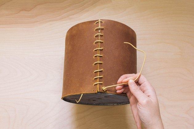 Attacher un double nœud sur un cordon en cuir dans le trou inférieur de la jardinière enveloppée de cuir