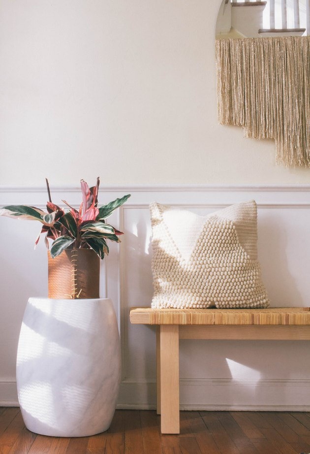 Jardinière enveloppée de cuir bricolage avec plante à feuilles roses et vertes sur un tabouret en marbre à côté du banc