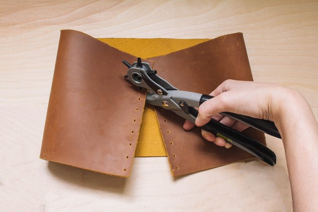 Perforation des trous sur les points marqués sur le cuir avec l'outil de perforation en cuir