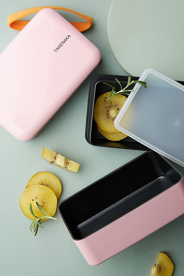 pink bento box with lid open and slices of fruit