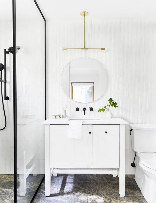 White modern Scandinavian bathroom vanity with white vanity, black steel-paned shower and brass pendant light