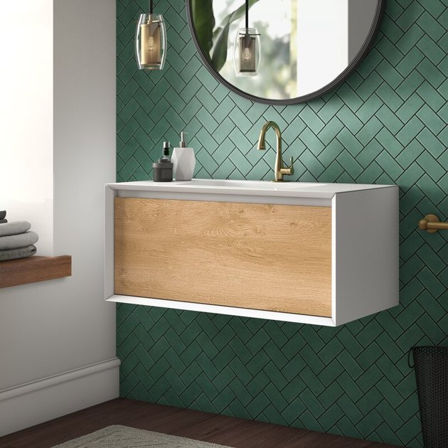 White and wooden wall-mounted Scandinavian bathroom vanity in a green tiled bathroom