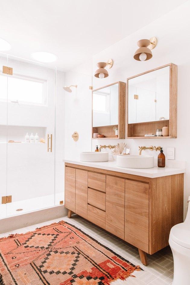 white Scandinavian bathroom vanity in teak with pink and red rug