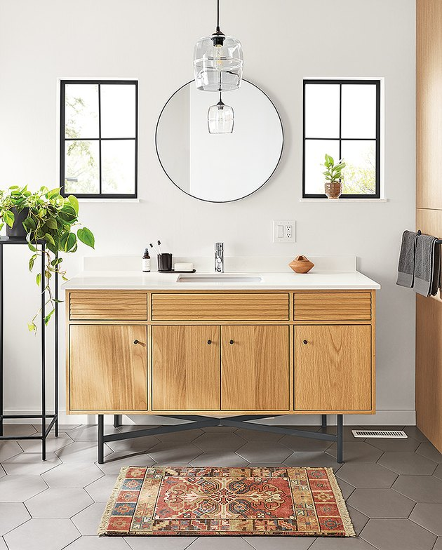 Wooden Scandinavian bathroom vanity in white bathroom with round mirror and colorful area rug