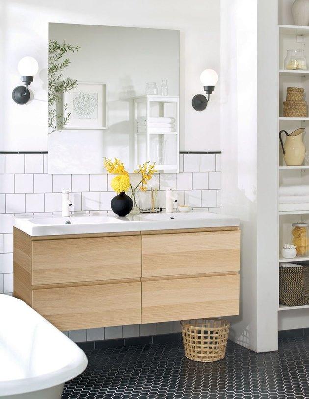 IKEA oak Scandinavian bathroom vanity in white bathroom with black floor tiles and large mirror