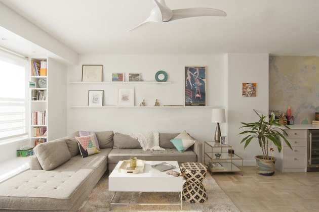 neutral living room with floating shelves and ceiling fan