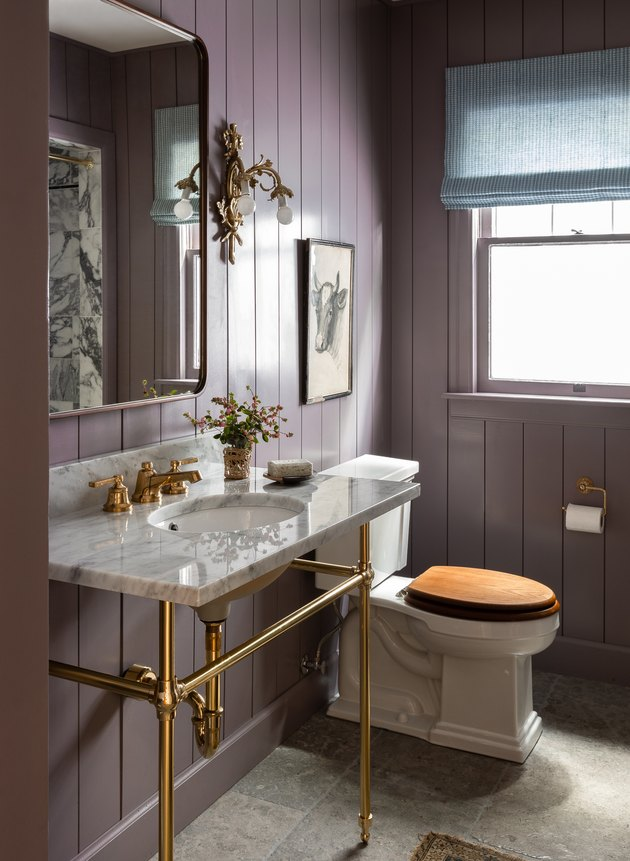 ornate gold trending bathroom lighting in bathroom with purple shiplap walls and marble sink