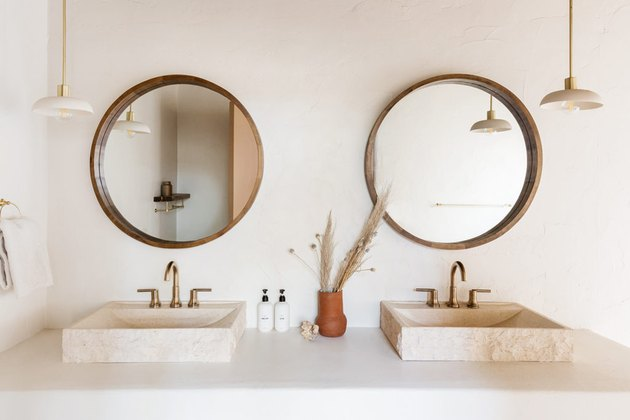 trending bathroom lighting in white bathroom with double vanity and circle mirrors