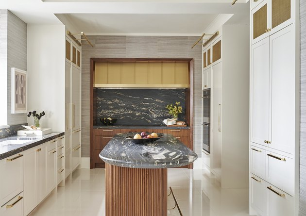 Art deco kitchen with marble backsplash and island and custom white cabinets
