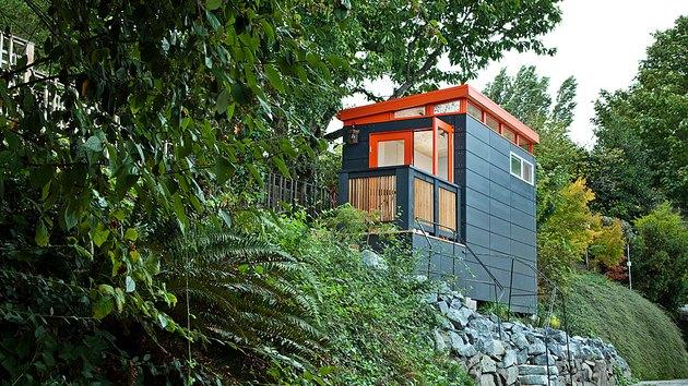 Hangar moderne peint en orange et turquoise sur le flanc de la colline