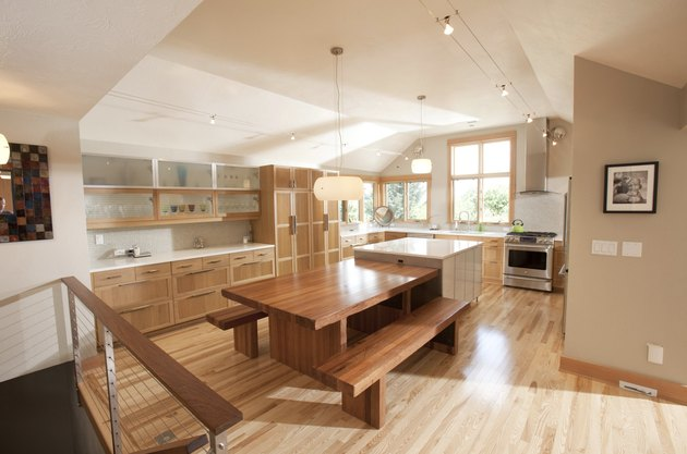 wooden kitchen island table in kitchen vaulted ceilings and polished wood floors