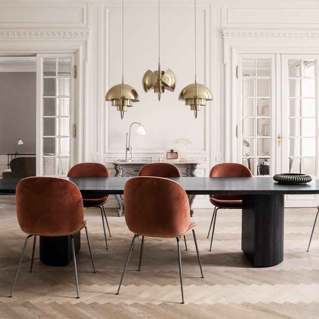 art deco dining room with brass pendants hanging above dining table
