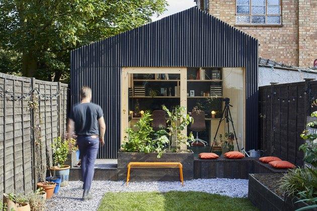 Remise moderne avec extérieur en panneau noir linéaire et accents en bois naturel
